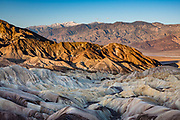Cresting the Panamint Range, snow-dusted Telescope Peak (11,043 ft) rises to the highest point in Death Valley National Park (Inyo County, California, USA). Photographed from Zabriskie Point at sunrise, 2018 April 20. Telescope Peak has one of the greatest vertical rises above local terrain of any mountain in the contiguous United States. Its summit rises 11,325 feet above the lowest point in Death Valley, Badwater Basin at −282 feet, in about 15 miles, and about 10,000 feet above the floor of neighboring Panamint Valley in about 8 miles.