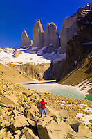 Hiker views the Towers of Paine (gigantic granite monoliths), Torres del Paine National Park, Patagonia, Chile