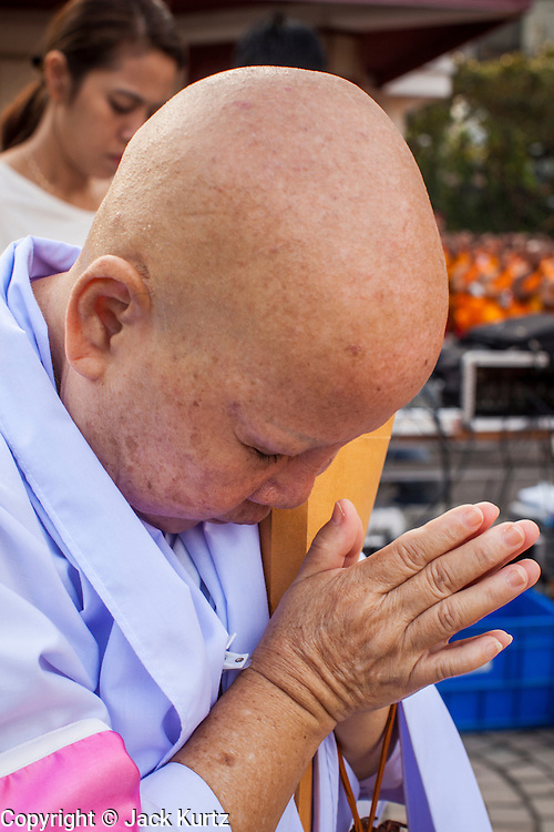 20 OCTOBER 2012 - BANGKOK, THAILAND:  A Buddhist nun prays at a special alms giving ceremony. More than 2,600 Buddhist Monks from across Bangkok and thousands of devout Thai Buddhists attended the mass alms giving ceremony in Benjasiri Park in Bangkok Saturday morning. The ceremony was to raise food and cash donations for Buddhist temples in Thailand's violence plagued southern provinces. Because of an ongoing long running insurgency by Muslim separatists many Buddhist monks in Pattani, Narathiwat and Yala, Thailand's three Muslim majority provinces, can't leave their temples without military escorts. Monks have been targeted by Muslim extremists because, in the view of the extremists, they represent the Thai state.         PHOTO BY JACK KURTZ