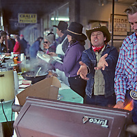 WHITEFISH, MONTANA. Sidewalk vendors cook up burgers for parade crowd at Winter Carnival.