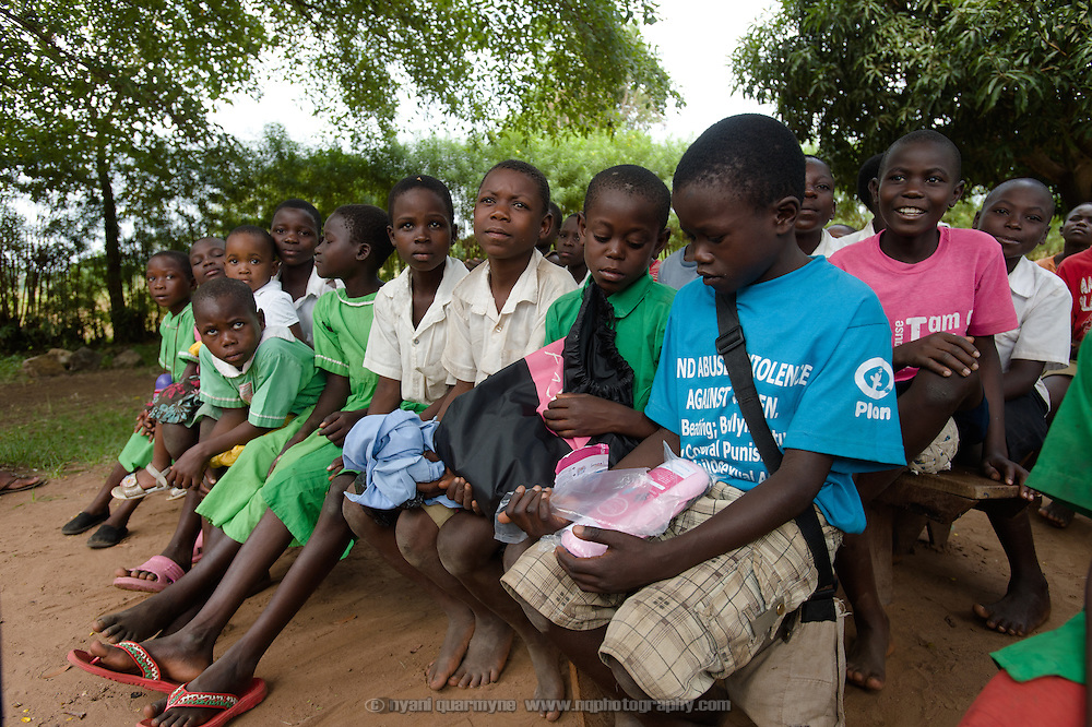 Given them to hold while the presenter's hands were full, boys look curiously at a pack of Afripads as Lovisa Wankya, a teacher and an Afripads dealer, demonstrates the correct use of Afripads to students at Achilet Primary School near Tororo in Eastern Uganda on 1 August 2014. Afripads are reusable fibre sanitary pads that are having a revolutionary impact on menstrual hygiene management, particularly amongst girls and women who cannot afford expesive disposable pads, and who previously had to use rags, cotton wool or toilet paper.