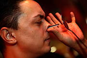 A performer banging a teaspoon op his nose without any ill effects