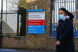 © Licensed to London News Pictures. 20/12/2020. London, UK. A woman wearing a face covering walks past the signage for the North Middlesex Hospital in Edmonton, north London. London hospitals have started to cancel operations and are redeploying NHS staff to cope with the increased demand from COVID-19 patients. Junior doctors at North Middlesex Hospital have been told to help look after patients on medical wards as part of plans by the Hospital to cope with rising numbers of coronavirus patients as London moves into Tier four restrictions. Photo credit: Dinendra Haria/LNP