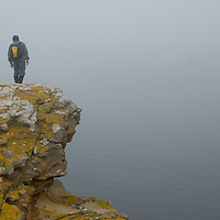 A Geo tourist stands atop a promintory called the Devil's Nose at West Point Island in Britain's  Falkland Islands.