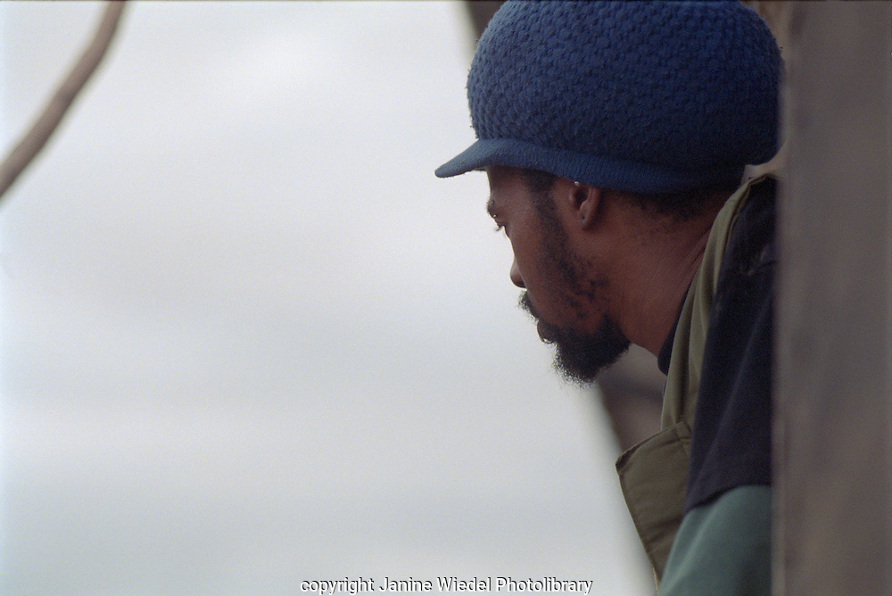 Rastafarian looking out window from squat