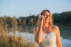 Cheerful woman smiling while talking on smart phone at riverbank, Bavaria, Germany