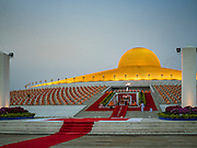 """22 FEBRUARY 2016 - KHLONG LUANG, PATHUM THANI, THAILAND: Monks sit around the chedi and listen to the abbot (in the center of the frame) during the Makha Bucha Day service at Wat Phra Dhammakaya.  Makha Bucha Day is a public holiday in Cambodia, Laos, Myanmar and Thailand. Many people go to the temple to perform merit-making activities on Makha Bucha Day, which marks four important events in Buddhism: 1,250 disciples came to see the Buddha without being summoned, all of them were Arhantas, Enlightened Ones, and all were ordained by the Buddha himself. The Buddha gave those Arhantas the principles of Buddhism, called """"The ovadhapatimokha"""". Those principles are:  1) To cease from all evil, 2) To do what is good, 3) To cleanse one's mind. The Buddha delivered an important sermon on that day which laid down the principles of the Buddhist teachings. In Thailand, this teaching has been dubbed the """"Heart of Buddhism."""" Wat Phra Dhammakaya is the center of the Dhammakaya Movement, a Buddhist sect founded in the 1970s and led by Phra Dhammachayo. The temple is famous for the design of its chedi, which some have likened to a flying saucer or UFO.      PHOTO BY JACK KURTZ"""