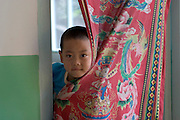 (MODEL RELEASED IMAGE). Cui Yuqi, 6, looks out from a curtain separating his bedroom from the main room. (Supporting image from the project Hungry Planet: What the World Eats.)