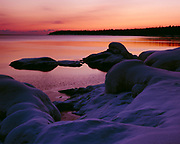 Pastel colors following sunset reflected in calm waters of Lake Superior during winter freeze-up, Cascade River State Park, Minnesota.