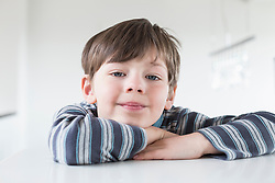 Portrait of boy leaning on table, close up
