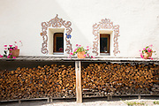 Woodpile at house in the Engadine Valley village of Guarda with old painted stone 17th Century buildings, Switzerland