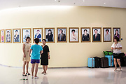Employees walk past photographs of sales representatives at the Tiens Group headquarters in Tianjin, China on Tuesday, Aug. 9, 2016. Tiens is a direct sales firm specializing in health and beauty products.