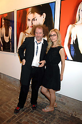 MIKE FIGGIS and model SOPHIA PUNCOCHAROVA in front of a photograph of her at the launch of 'Glenmorangie 5 Senses' an exhibition of photographs by Mike Figgis held at Proud Camden, Stables Market, London NW1 on 13th May 2008.<br /><br />NON EXCLUSIVE - WORLD RIGHTS