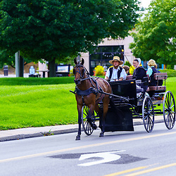 Intercourse, PA, USA - August 30, 2020: An Amish family uses a horse drawn wagon to travel a rural road in Lancaster County on a sunny Sunday afternoon.