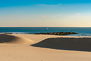 The golden glow of the morning sun on the winter beach in Spring Lake, NJ USA