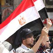 Two friends, demonstrating in Cairo's Tahrir Square, raise their national flags with pride.