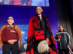 US President Barack Obama receives a traditional blanket and hat during the 2016 White House Tribal Nations Conference at the Andrew W. Mellon Auditorium, September 26, 2016, Washington, DC. The conference provides tribal leaders with opportunity to interact directly with federal government officials and members of the White House Council on Native American Affairs. (Pool/Aude Guerrucci)