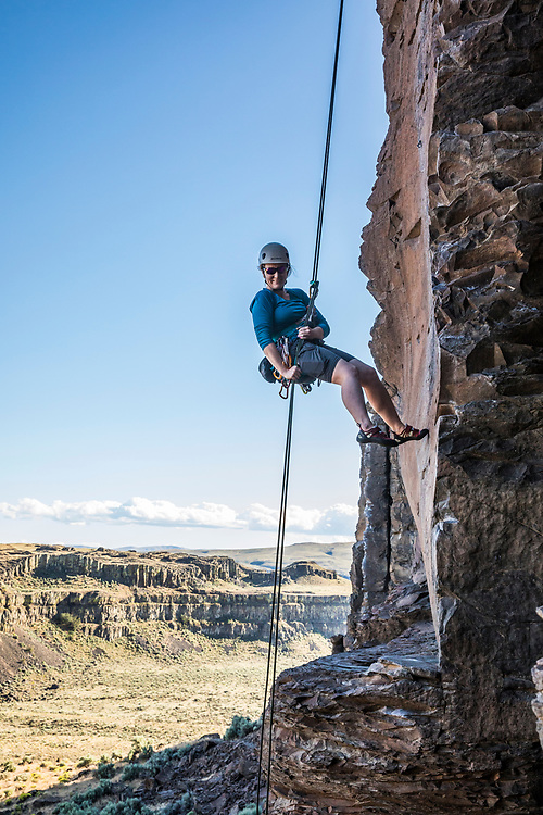 A middle aged woman rappelling from a rock climb in Echo Basin near Frenchmans Coulee, Eastern Washington, USA.