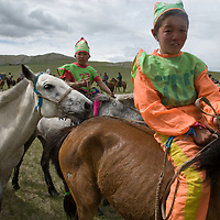 Young, costumed, bareback boys & girls after a 20km race at a traditional naadam festival on a remote pass near Muren, Mongolia.