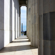 The Washington Monument is seen through the giant columns of the Lincoln Memorial, which honors the 16th President of the United States. Located on the National Mall in Washington, DC, the Lincoln Memorial contains a large seated sculpture of Abraham Lincoln and inscriptions of two well-known speeches by Lincoln, The Gettysburg Address and his Second Inaugural Address.