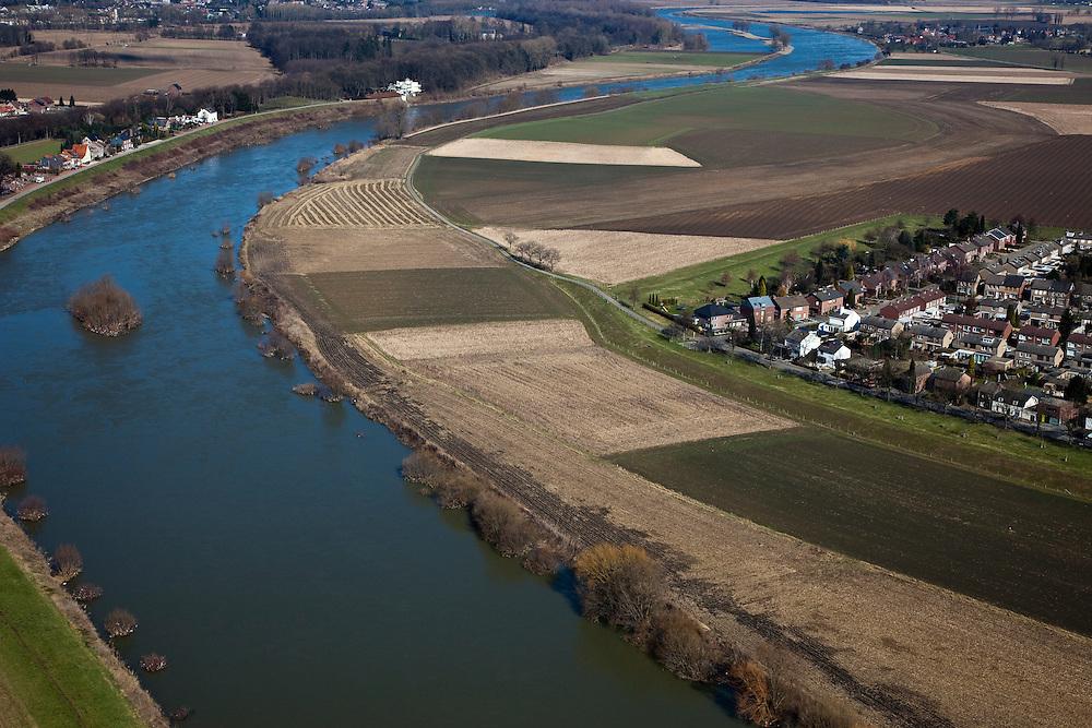 Nederland, Limburg, gemeente Maastricht, 07-03-2010; Borgharen, kerkdorp aan de Maas die hier de grens met Belgie vormt (l). Sinds de overstromingen in de jaren '90 is het dorp rondom voorzien van dijken. In het kader van het Grensmaasproject worden de uiterwaarden (weerden) ten westen en ten noorden van het dorp afgegraven en de stroomgeul van de Maas wordt verbreed.   .Borgharen, the parish, the river Meuse who forms the border with Belgium (l). Since the floods in the 90s, dikes have been build around village. Under the Grensmaas (Border Meuse) projec, the Meuse floodplains (wards) north of the village will be excavated and the flow channel of the Meuse will be broadened..luchtfoto (toeslag), aerial photo (additional fee required).foto/photo Siebe Swart