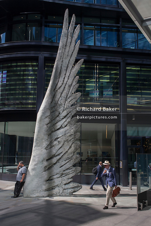 City workers pass-by the giant artwork of a bronze wing<br /> during a spring lunchtime in London's financial district, on 4th July, London, United Kingdom. As light reflects off nearby office buildings, the lunchtime crowd walk past this giant artwork on their way to meetings and sandwich bars. The ten-metre-tall bronze sculpture is by President of the Royal Academy of Arts, Christopher Le Brun, commissioned by Hammerson in 2009. It is called 'The City Wing' and has been cast by Morris Singer Art Founders, reputedly the oldest fine art foundry in the world. (Photo by Richard Baker / In Pictures via Getty Images)