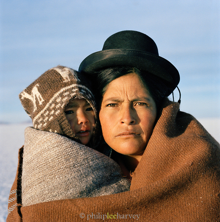 Portrait of woman with young boy in traditional dress on Salar de Uyuni salt flats, Potosi, Bolivia. The Salar de Uyuni are the worlds largest salt flats.