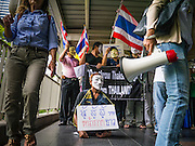 """02 JUNE 2013 - BANGKOK, THAILAND:   A legless man leads a protest march through the Bangkok skywalk system. The so called White Mask protesters are strong supporters of the Thai monarchy. About 300 people wearing the Guy Fawkes mask popularized by the movie """"V for Vendetta"""" and Anonymous, the hackers' group, marched through central Bangkok Sunday demanding the resignation of Prime Minister Yingluck Shinawatra. They claim that Yingluck is acting as a puppet for her brother, former Prime Minister Thaksin Shinawatra, who was deposed by a military coup in 2006 and now lives in exile in Dubai.   PHOTO BY JACK KURTZ"""