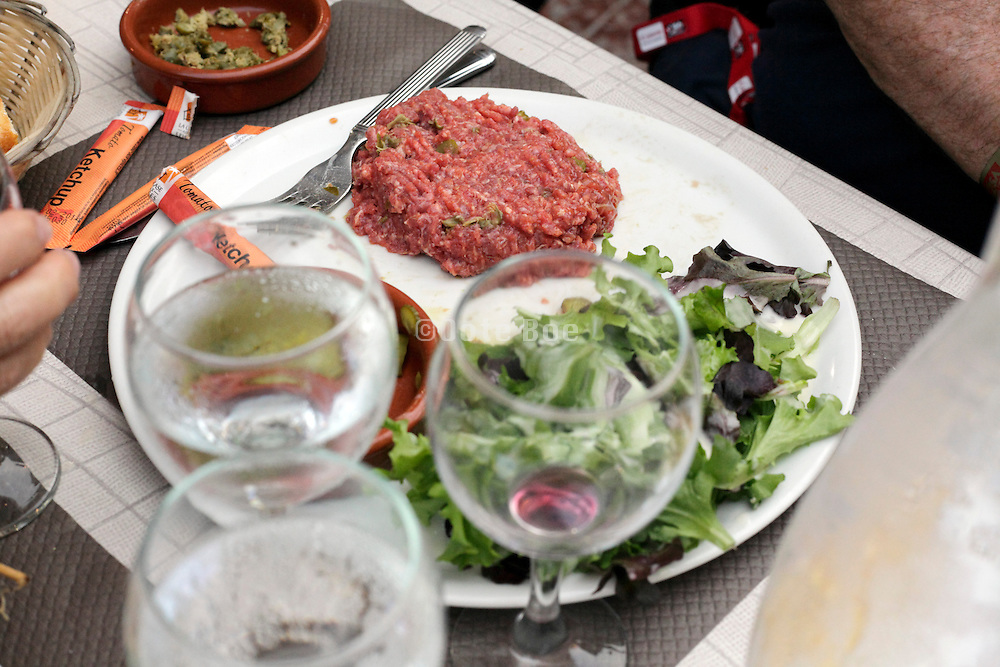 beef tartare with salad water and wine glass