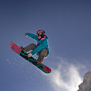 A young snowboarder takes to the air at The Remarkables Ski Fields, Queenstown, New Zealand during a session with 'The Air Bag'  a large inflatable airbag which breaks the fall of the participant on landing and allows valuable experience and a training aid for Aerial skiers and snowboarders. Queenstown, South Island, New Zealand, 18th July 2011