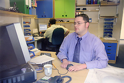 Man with disability; who is wheelchair user; working at computer in office,
