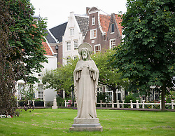Statue in courtyard at the ancient Begijnhof n Amsterdam, The Netherlands