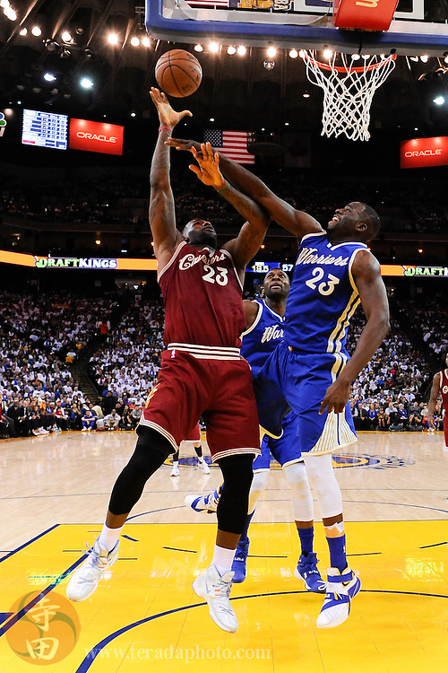 December 25, 2015; Oakland, CA, USA; Cleveland Cavaliers forward LeBron James (23, left) shoots the basketball against Golden State Warriors forward Draymond Green (23, right) during the third quarter in a NBA basketball game on Christmas at Oracle Arena. The Warriors defeated the Cavaliers 89-83.