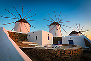 """Mykonos windmills - The windmills are a defining feature of the Mykonian landscape. There are many dotted around the island, but most are concentrated in the main town of Chora. The famous """"Kato Mili"""" in Chora (Greek for lower mills), stand in a row on a hill overlooking the sea to harness the strong northern winds. Capped with wood and straw, the windmills were built by the Venetians in the 16th century to mill flour and remained in use until the early 20th century. Many have been refurbished and restored to serve as homes to locals and vaults to numerous Mykonian heritage documents."""