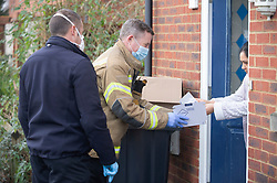 © Licensed to London News Pictures 02/02/2021.        Maidstone, UK. A firefighter collecting tests from a household. Door to door testing for the South African variant of Covid-19 has started in the Maidstone area of Kent this afternoon. Police, Fire and NHS staff along with volunteers from Kent Search and Rescue and Kent County Council are handing out PCR tests to residents than collecting them an hour later. Photo credit:Grant Falvey/LNP