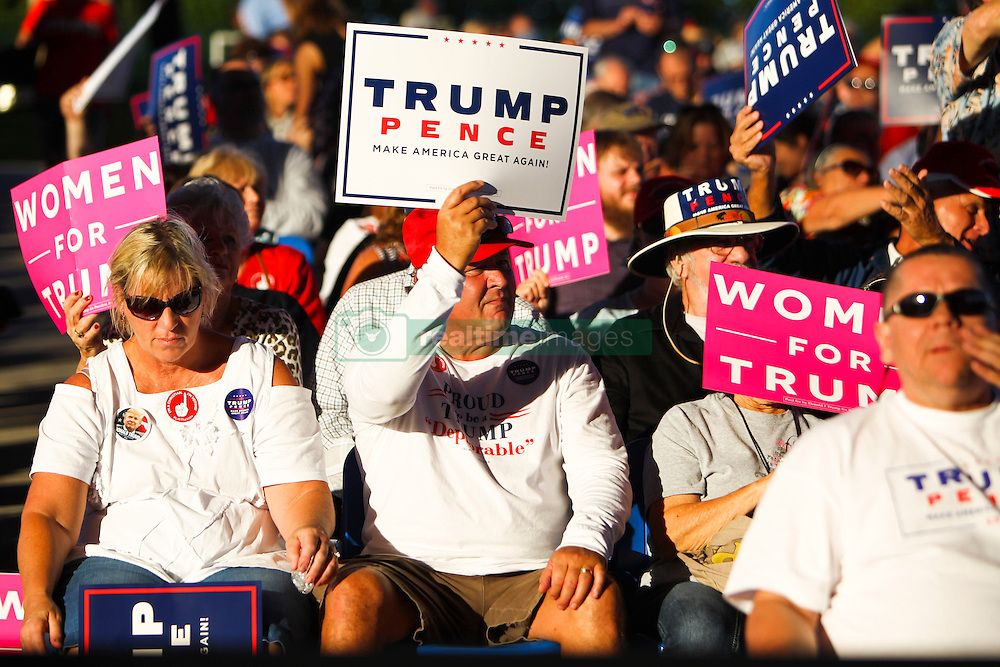 October 24, 2016 - Tampa, Florida, U.S. - WILL VRAGOVIC       Times.Phil Vernier, 60, of Tampa hoist a Trump-Pence sign before the Trump rally at the MidFlorida Credit Union Amphitheatre in Tampa, Fla. on Monday, Oct. 24, 2016. ''I heard it was an inspiring event,'' Vernier said, ''I've never attended one (a political rally) before. Trump needs our support. (Credit Image: © Will Vragovic/Tampa Bay Times via ZUMA Wire)