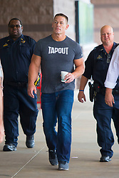 EXCLUSIVE: WWE wrestling star John Cena arrives at a movie theatre in New Orleans with police and his entourage before attending a viewing of his new movie 'Blockers'. Cena could be seen holding a coffee cup as his muscles bulged out of his 'Tapout' t-shirt. Cena is in town to attend WWE Wrestlemania 34, 2018. 06 Apr 2018 Pictured: John Cena. Photo credit: MEGA TheMegaAgency.com +1 888 505 6342