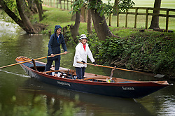 © Licensed to London News Pictures. 04/06/2021. London, UK. Members of the public are seen rowing a barge on the River Cherwell past Oxford Botanic Gardens, in central Oxford, England, on a wet and overcast day. The UK is experiencing damp and overcast conditions following a week of annual high temperatures. Photo credit: Ben Cawthra/LNP