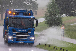 Licensed to London News Pictures. 12/07/2021. London, UK. Walkers and runners get caught in torrential rain in Richmond Park, southwest London this afternoon with roads and pavements becoming quickly flooded as the Met Office issue yellow weather warnings for heavy rain and thunderstorms which may cause disruption to travel and flooding. However, sunshine and warm weather is predicted for the rest of the week with highs of 26c for the weekend.. Photo credit: Alex Lentati/LNP