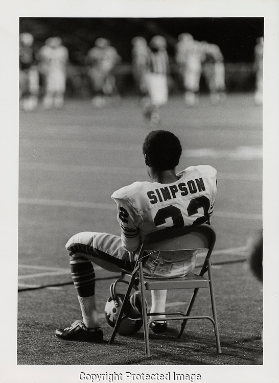 """O.J. Simpson, """"The Juice"""" sits on the sideline during a game between the Buffalo Bills and the Washington Redskins in August 1970.  Photograph by Dennis Brack"""
