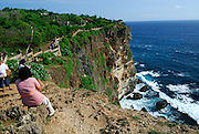 Tourists standing on edge of cliff, having climbed beyond safety fence, with clifftops and crashing surf in background. Uluwatu Temple, Bali, Indonesia.