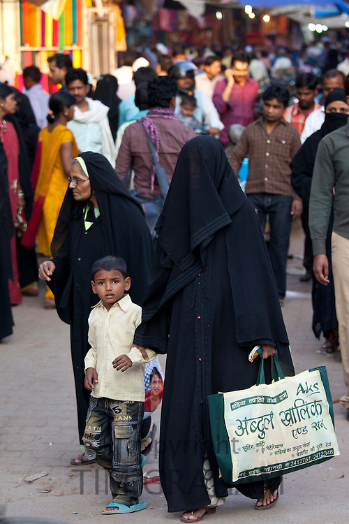 Street scene in holy city of Varanasi, muslim woman in black veil burkha shopping with her child, India