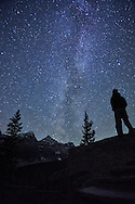 A man looks up at the night sky to see the Milky Way galaxy in Banff National Park, Alberta, Canada.