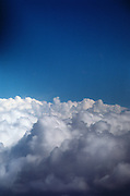 Cottony floor of white clouds extending towards clear blue sky.