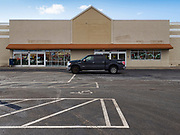 "26 FEBRUARY 2020 - FARMINGTON, MINNESOTA: A motorist drives past the closed Family Fresh Market grocery store Farmington, MN, about 30 minutes south of the Twin Cities. Farmington, with a population of 21,000, is a farming community that has become a Twin Cities suburb, the population has doubled since the 2000 census. The Family Fresh Market, Farmington's only grocery store, closed in December, 2019. The closing turned the town into a ""food desert."" The USDA defines food deserts as having at least 33% or 500 people of a census tract's population in an urban area living 1 mile from a large grocery store or supermarket. Grocery chains Hy-Vee and Aldi both own land in Farmington but they have not said when they plan to build or open stores in the town.     PHOTO BY JACK KURTZ"