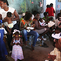 Mothers and children gather for a free meal after the 'Celebration of Life' ceremony in Trou-du-Nord, Haiti.
