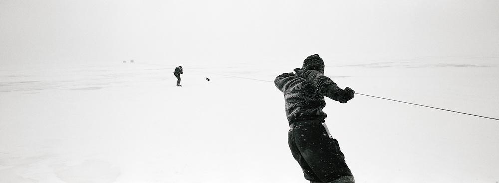 Fishermen dragging nets under the ice at Lake Baikal, Siberia, Russia