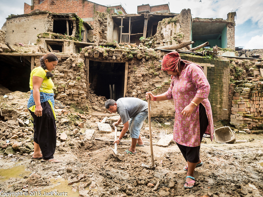 04 AUGUST 2015 - KHOKANA, NEPAL: Homeowners remove earthquake debris from the street in front of their home in Khokana, a village about an hour from Kathmandu. Three months after the earthquake, roads in many rural villages are still blocked by earthquake debris. The Nepal Earthquake on April 25, 2015, (also known as the Gorkha earthquake) killed more than 9,000 people and injured more than 23,000. It had a magnitude of 7.8. The epicenter was east of the district of Lamjung, and its hypocenter was at a depth of approximately 15km (9.3mi). It was the worst natural disaster to strike Nepal since the 1934 Nepal–Bihar earthquake. The earthquake triggered an avalanche on Mount Everest, killing at least 19. The earthquake also set off an avalanche in the Langtang valley, where 250 people were reported missing. Hundreds of thousands of people were made homeless with entire villages flattened across many districts of the country. Centuries-old buildings were destroyed at UNESCO World Heritage sites in the Kathmandu Valley, including some at the Kathmandu Durbar Square, the Patan Durbar Squar, the Bhaktapur Durbar Square, the Changu Narayan Temple and the Swayambhunath Stupa. Geophysicists and other experts had warned for decades that Nepal was vulnerable to a deadly earthquake, particularly because of its geology, urbanization, and architecture.     PHOTO BY JACK KURTZ