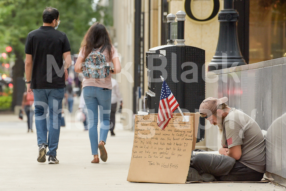 Homeless veteran and Pedestrians, shoppers and tourist along Michigan Avenue in Chicago, Illinois. Photo by Mark Black