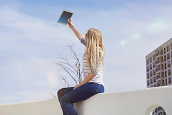 Teenage girl sitting on a wall and taking selfie with digital tablet, Munich, Bavaria, German